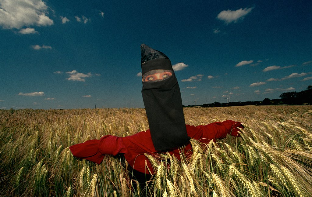 A scarecrow with a niqab in a field of wheat