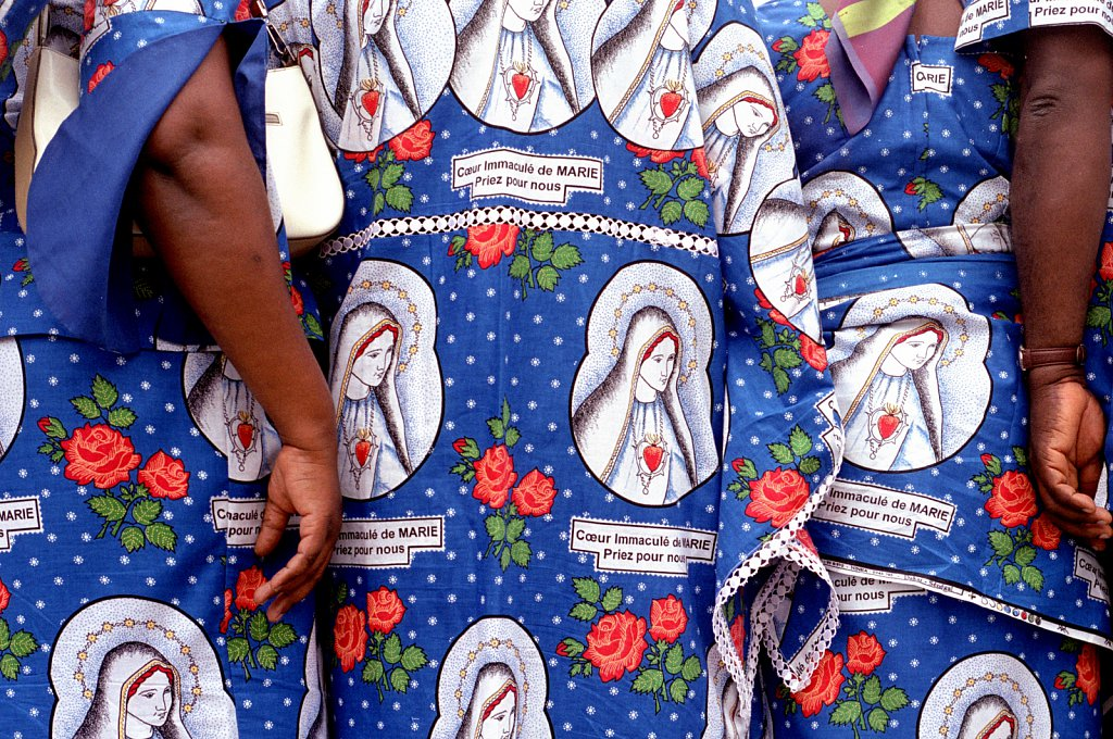 Worshippers to Lourdes from the Ivory Coast wearing dresses patterned with an image of the Virgin.