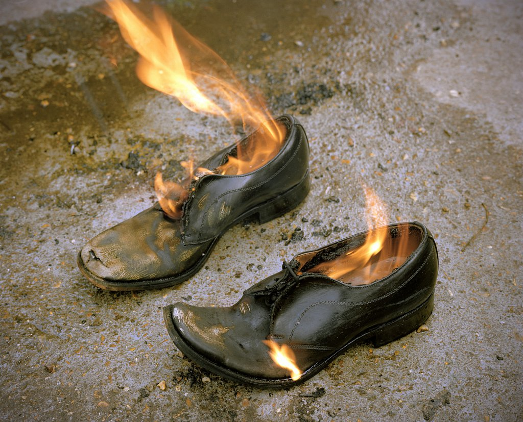 Shoes being burnt after a car boot sale, Bootle,Merseyside, UK.